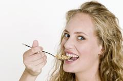 Young woman eating crunchy muesli with a spoon Stock Photos
