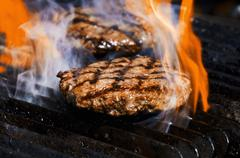 Flame grilled burgers on the grill - stock photo