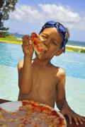 Boy with swimming goggles on head eating pizza on beach - stock photo