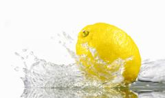 Lemon with splashing water - stock photo