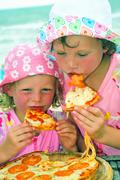 Two children eating pizza on the beach - stock photo