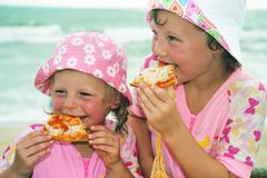 Children eating pizza by the sea Stock Photos
