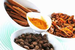 Curry powder, cardamom, cinnamon sticks, mace Stock Photos