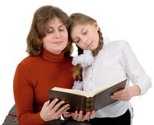 Woman with girl reading book Stock Photos
