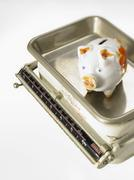 Piggy bank on kitchen scales - stock photo