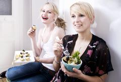 Two women eating appetisers Stock Photos