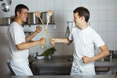 Two chefs fencing with wooden spoons in commercial kitchen - stock photo