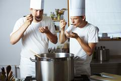 Two chefs tasting soup out of pan - stock photo