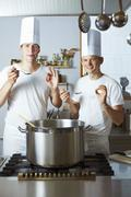Two chefs satisfied with the results of their culinary skills - stock photo