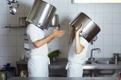 Two chefs having discussion with large pans on their heads - stock photo