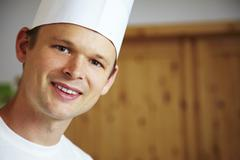 Young chef looking into camera - stock photo
