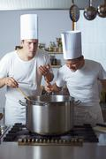 Two chefs standing by range - stock photo