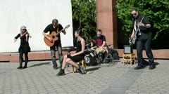 Rock band with woman vocalist play music and sing near church. Stock Footage