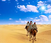 Tourist riding camel in Sahara desert Stock Photos