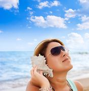 woman listening counch shell sound - stock photo