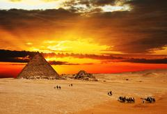 Camel caravan going through desert in front of pyramid at sunset Stock Photos