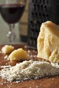 Grated Romano Cheese with Cheese Grater and Glass of Red Wine Stock Photos