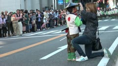 Woman fixes a young boy's hat during a traditional parade in Japan Stock Footage