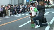 Stock Video Footage of Woman fixes a young boy's hat during a traditional parade in Japan