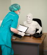 Patient similar to a mummy and the doctor Stock Photos