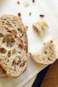 Two Slices of Artisan Bacon Bread with Crumbs on a White Napkin - stock photo
