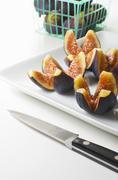 Fresh Figs Quartered on a White Dish; Knife; Basket of Fresh Figs - stock photo