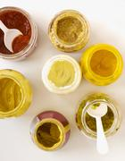 Assorted Open Condiment Jars; From Above; Mustards, Mayonnaise, Salsa and Relish - stock photo