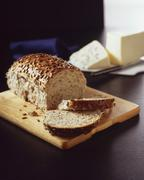 Partially Sliced Loaf of Multi Grain Bread on a Cutting Board; Cheese Stock Photos