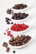Allspice berries, pink pepper, juniper berries, black peppercorns on sppons Stock Photos