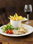 Chicken breast with garlic, chips and a glass of red wine - stock photo
