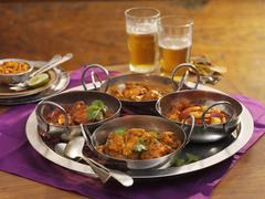 Four different types of curries on a tray Stock Photos