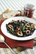 Black tagliatelle with squid and chilli sauce Stock Photos