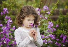 A little girl smelling flowers in a garden - stock photo