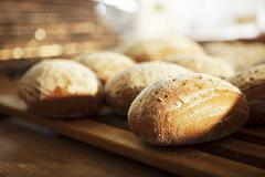 Bread rolls on a wooden rack Stock Photos