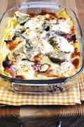 Lasagne with artichokes and ham in a baking dish - stock photo