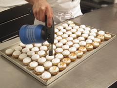 Lemon cupcakes being caramelised with a gas burner - stock photo