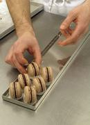 Chocolate macaroons being arranged on a baking tray - stock photo