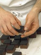 Chocolate cubes being placed into praline cases - stock photo