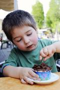 A little boy eating chocolate ice cream in an ice cream cafe - stock photo
