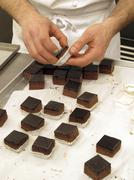 Chocolate cubes being added to praline cases - stock photo