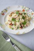 Farfalle with bacon, peas and parsley Stock Photos