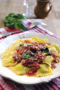 Spinach and ricotta filled ravioli pasta with tomato and fresh basil sauce - stock photo