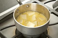 Melting Butter in a Pot on the Stove Stock Photos