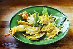 Ravioli filled with courgette and courgette flowers - stock photo