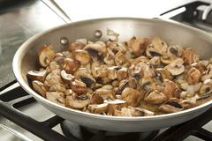 Mushrooms and Onions Cooking in a Skillet Stock Photos