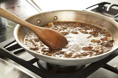 Making Mushroom Wine Sauce in a Skillet - stock photo
