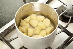 Peeled and Chopped Potatoes in a Pot of Water for Boiling - stock photo