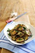 Fried Jerusalem artichoke slices with garlic and parsley - stock photo