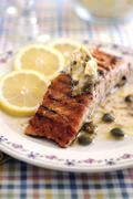 Fried salmon fillet with anchovies and caper butter Stock Photos