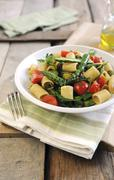 Pasta with cherry tomatoes, green asparagus and rocket - stock photo